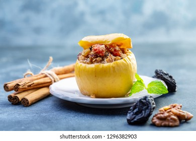 Baked apple stuffed with oat flakes, dried apricots, raisins, prunes, honey and cinnamon in a plate on a gray textured background, selective focus.