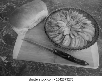 baked apple tart on chopping board alongside a fresh baked loaf of bread and a black handled bread knife. Also monochrome