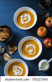 Baked apples and pumpkin soup with sage butter on blue table a top view. Seasonal comfort food.