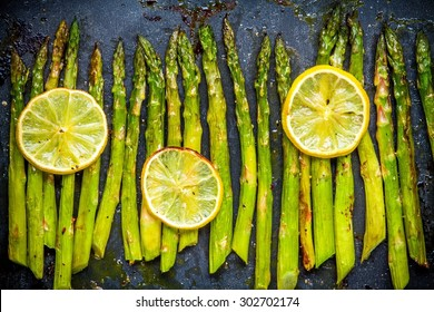 baked asparagus with lemon on a dark background