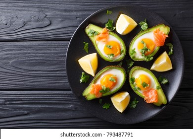 Baked avocado with egg, smoked salmon and greens close-up on a plate on a table. horizontal top view from above background