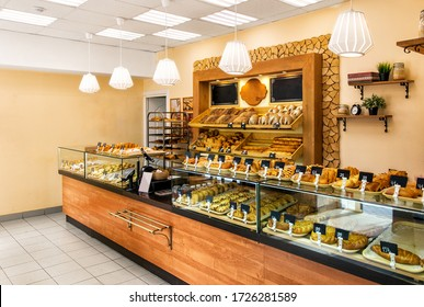 Baked baguettes and pies on showcase in bakery shop. Inscriptions in russian with the name baking: cheesecake, bun, pie, baguette and others