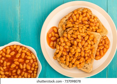 Baked Beans in Tomato Sauce on Toast On A Blue Wooden Background With Copy Space