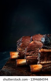 Baked beef brisket on the ribs smoked with a dark crust on a wooden Board. Classic Texas BBQ