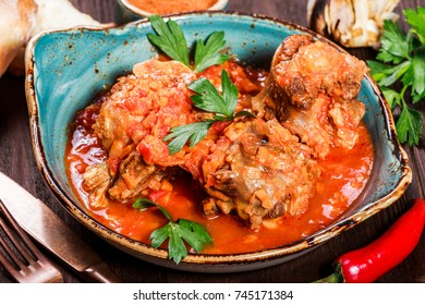 Baked beef with vegetables served with fork, bread, spices on wooden background. Hot Meat Dishes. Caucasian food. Top view