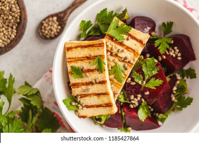 Baked beet salad with grilled tofu parsley and oil in a white bowl. Healthy vegan food concept.