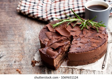 Baked  belgian chocolate cheesecake with chocolate ganache on wooden table