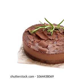 a  baked belgian chocolate cheesecake with rosemary topped with chocolate ganache