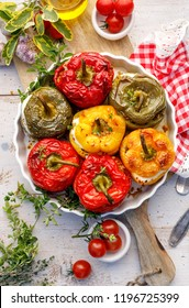 Baked bell peppers stuffed. Mushrooms, rice,  cheese and herbs stuffed peppers in a baking dish on a white wooden table. A healthy and delicious vegetarian dish.