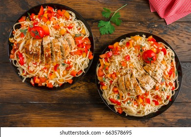 Baked boneless skinless chicken  breasts and pasta salad with fresh vegetables on the black plates on the wooden rustic table, top view.