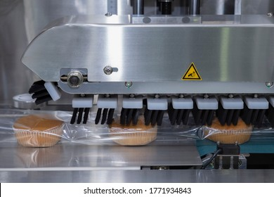 baked bread in food grade plastic bag on conveyor belt moves to seal in packing machine at production line of bakery manufacturing factory. food processing and industry concept