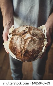 Baked bread of sourdough in hands - The bread of sourdough, homemade and natural creation. The sourdough has natural yeast, which makes the food healthier, as well as rich.