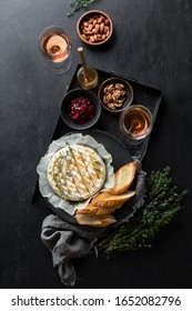 Baked brie served in a rustic manner with honey walnuts cranberry jam and rose wine, top down view of dark table setting