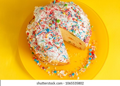Baked brightly decorated and colorful paska with candied fruit inside and without one piece of it placed on the plate on the yellow background