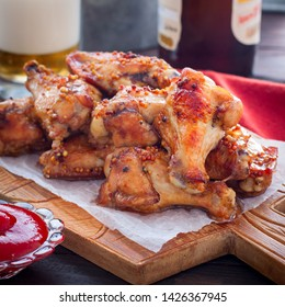 Baked Buffalo Beer Wings on a wooden board, square