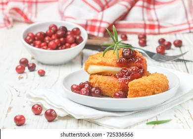 Baked Camembert (brie) with fresh berries and cranberry sauce with rosemary on a white plate. Gourmet appetizer. Breakfast. Selective focus