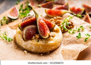 Baked camembert cheese with figs, walnuts, honey and thyme on the rustc background. Selective focus. Shallow depth of field.