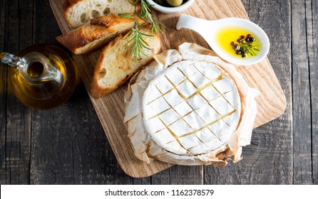 Baked camembert cheese. Fresh Brie cheese and a slice on a wooden board with nuts, honey, rosemary, baguette bread grilled toasts and leaves. Brie type of cheese. Italian, French cheese.