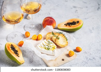 Baked camembert cheese with toasts, kumquat and papaya and glasses of wine