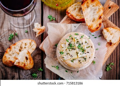 Baked camembert with toasts and thyme on rustic wooden table