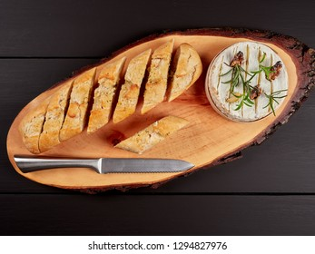 Baked Camembert with walnuts, rosemary stalks and garlic cloves, served with crusty garlic gread, on a rustic board, flat lay