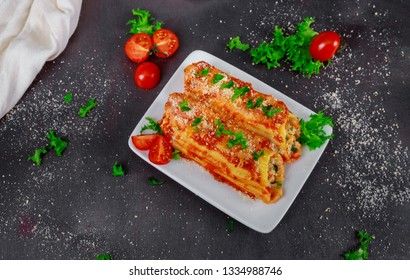 Baked cannelloni with cheese, tomatoes on a white plate