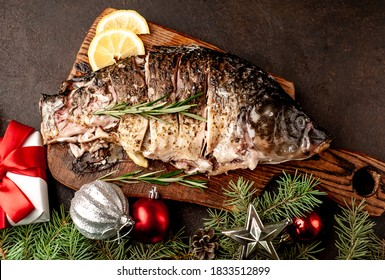 baked carp for the holiday of Christmas on a background of stone with Christmas trees and Christmas decorations.