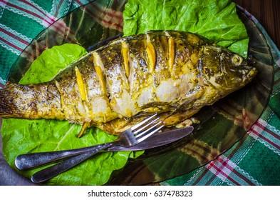 Baked carp with lemon on a plate