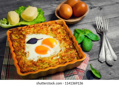 Baked casserole of grated potatoes with eggs sunny side up, cheese. Ingredients for casseroles potatoes - cheese, raw potatoes, eggs, lettuce, basil. Gray wooden rustic background.