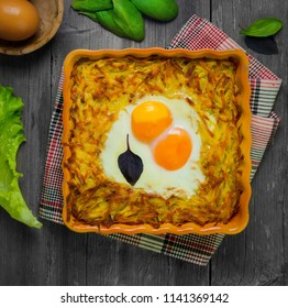Baked casserole of grated potatoes with eggs sunny side up, cheese. Ingredients for casseroles potatoes - cheese, raw potatoes, eggs, lettuce, basil. Gray wooden rustic background. Top view.