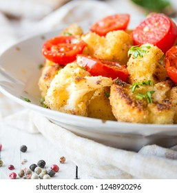 Baked cauliflower with tomatoes and herbs in a plate on white wooden table