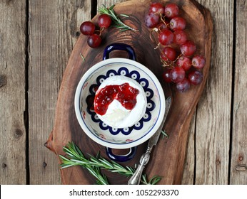Baked cheese Camembert with cranberry jam, grapes and rosemary on a wooden board. Selective focus, toned.