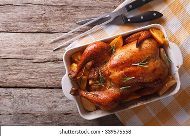 baked chicken with apples in the baking dish on a table. horizontal top view