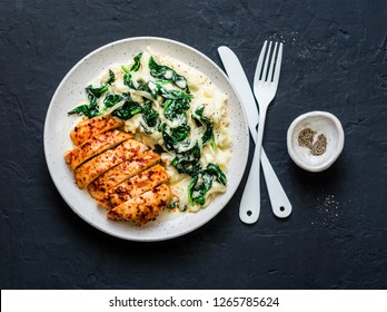 Baked chicken breast, mashed potatoes with creamy spinach on dark background, top view. Comfort food