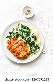 Baked chicken breast, mashed potatoes with creamy spinach on a light background, top view. Comfort food