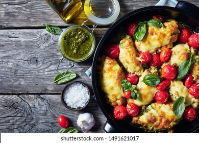 baked Chicken breast rolls filled with basil pesto, tomatoes and cheese in a black ceramic baking dish on an old wooden table, horizontal view from above, flatlay, free space, close-up