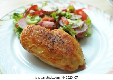 Baked chicken breast with vegetable salad on a white plate close up. Selective focus.