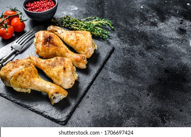Baked chicken drumstick, legs with herbs. Black background. Top view. Copy space