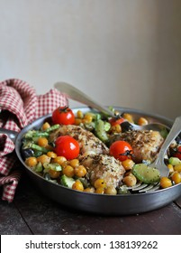 Baked chicken drumsticks with chickpea, courgette, eggplant and cherry tomatoes in a pan