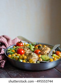Baked chicken drumsticks with chickpea, courgette, eggplant and cherry tomatoes in a pan, selective focus