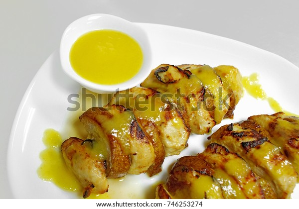 baked chicken fillet with pear and sauce on a white plate