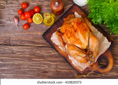 baked chicken with a golden crust with vegetables on a wooden background