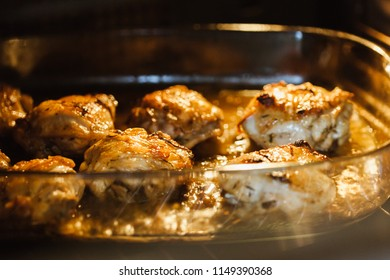 Baked chicken leg steak on white wine sauce and onions in glass baking dish inside the oven