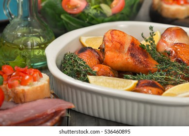 Baked chicken legs in a baking dish close up on the wooden table with variety food