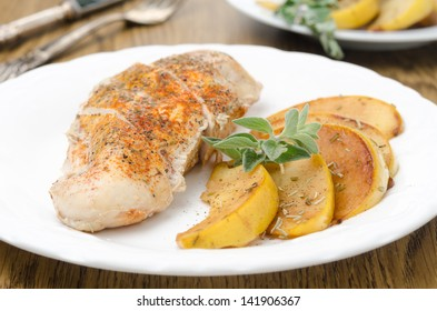 Baked chicken and saute quince with rosemary on a plate closeup