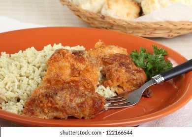 Baked chicken thighs with rice on a dinner plate