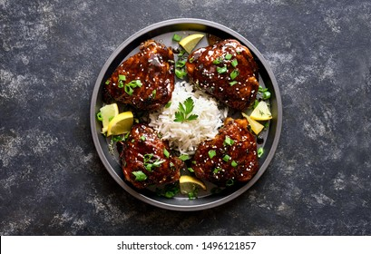 Baked chicken thighs with rice over dark stone table. Grilled chicken thighs in honey soy sauce. Tasty food in asian style. Top view, flat lay