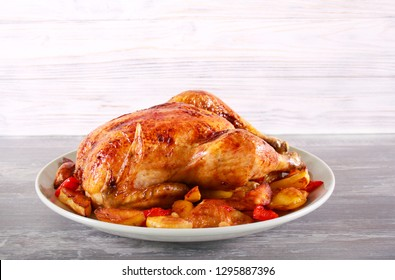 Baked chicken with vegetables on plate, wooden background