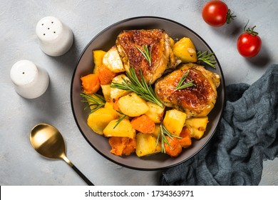 Baked chicken with vegetables. One pot dish. Baked in orange sauce. Top view on stone table.
