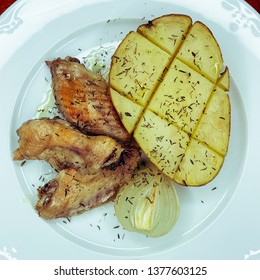 Baked chicken wings and drumsticks with potatoes and onions.